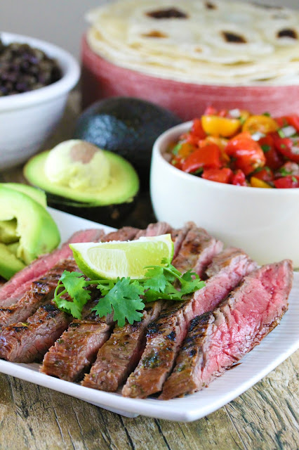 Sliced Authentic Carne Asada on a plate, with lime and cilantro on top on a table with avocados, tortillas, and some tomatoes