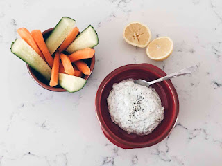 tzatziki dip in red bowl with vegetable sticks and lemon