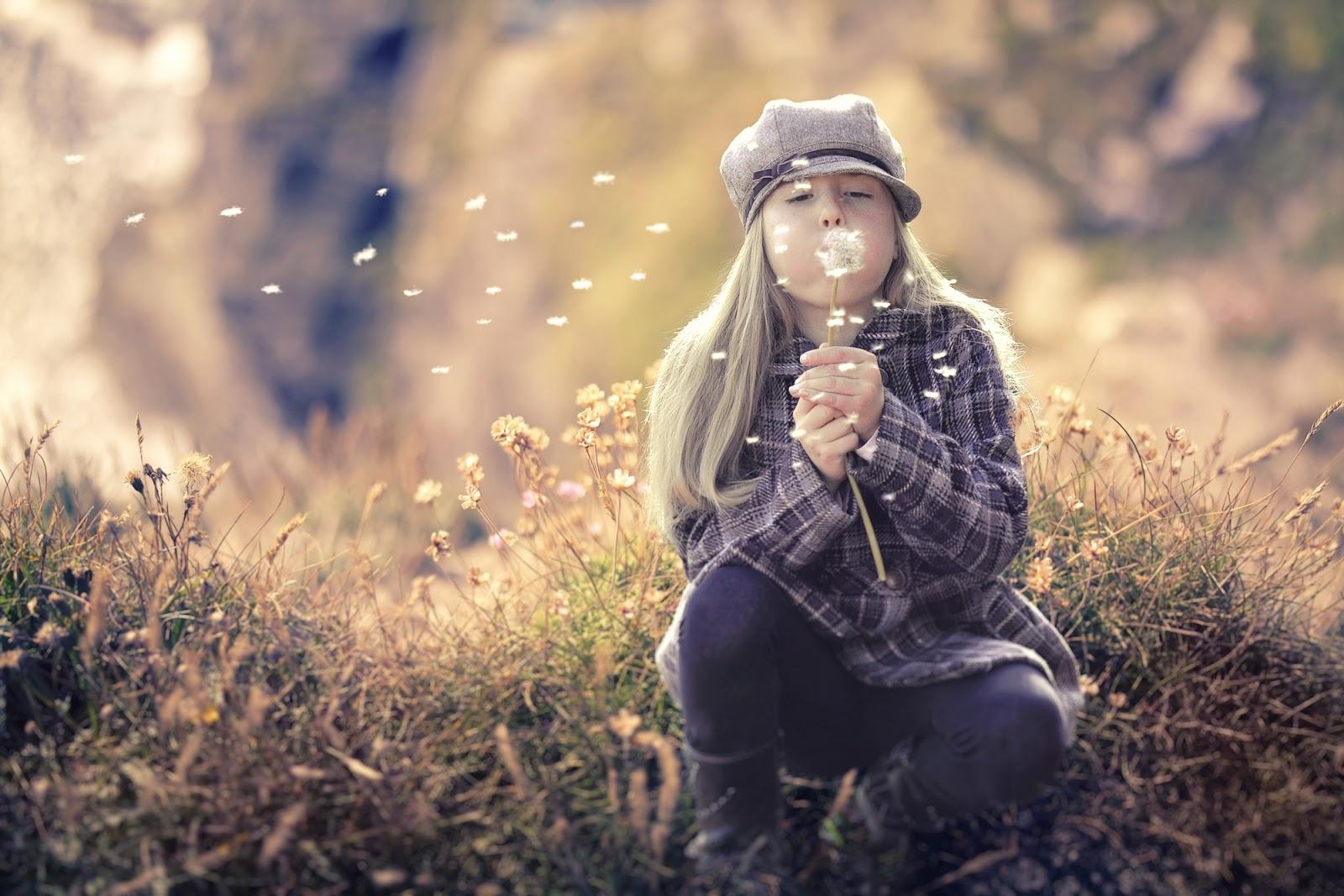 蒲公英の綿毛を吹く少女