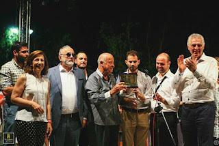 Ο Μίμης Πλέσσας κρατάει την πλακέτα γύρω του ο Π.Κουρουμπλής, ο Β.Αυγουλάς, ο Γ. Γαβράς, ο Α. Παχατουρίδης και η Μ. Τσιώτα