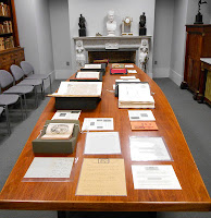 A photograph showing a long table of book and manuscript materials.