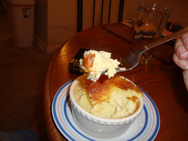 Parmesan and Gruyere Cheese Soufflé Being Eaten With A Fork