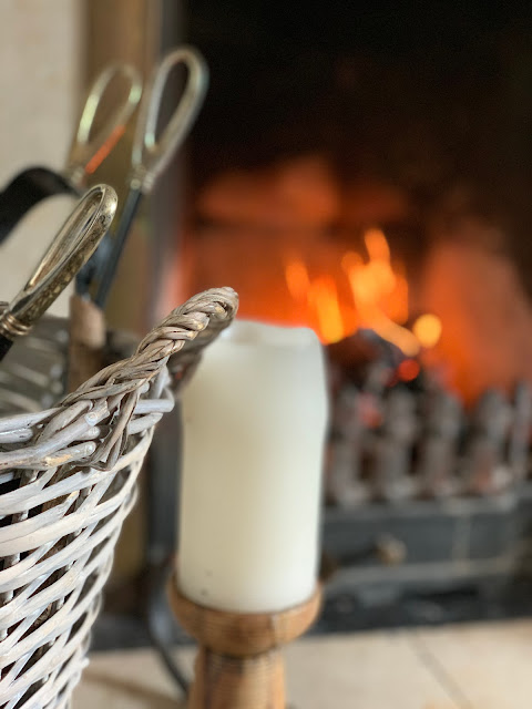 Log basket, church candle and log fire