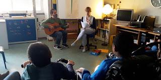 A professora conta sentada a história acompanhada do professor que toca uma guitarra e os alunos escutam com atenção.