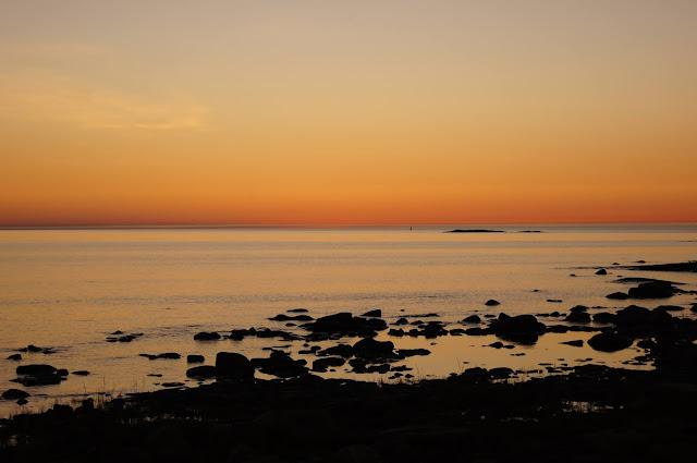 Kallioista merenrantaa auringonlaskussa