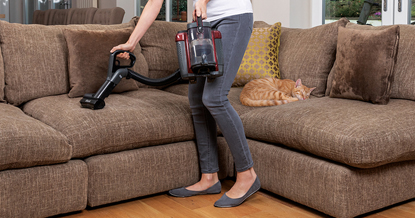 woman hoovering sofa that ginger tabby cat is sleeping on