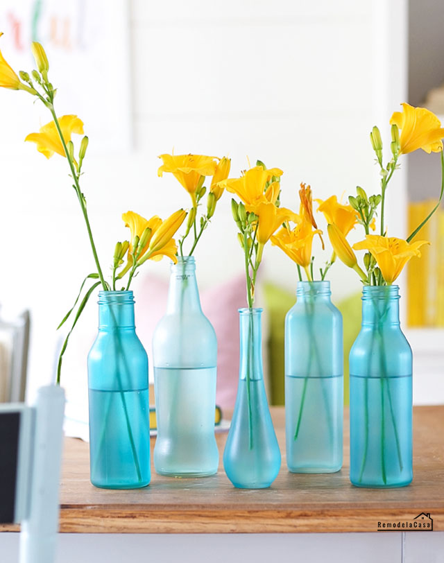 blue painted bottles with yellow flowers