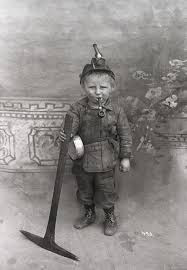 a young boy in the mines with a pipe and pickaxe