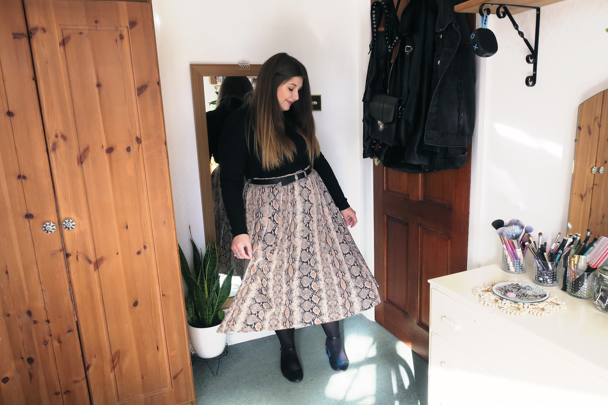 Grace is wearing a black roll neck top tucked in to a brown snakeskin print midi skirt.