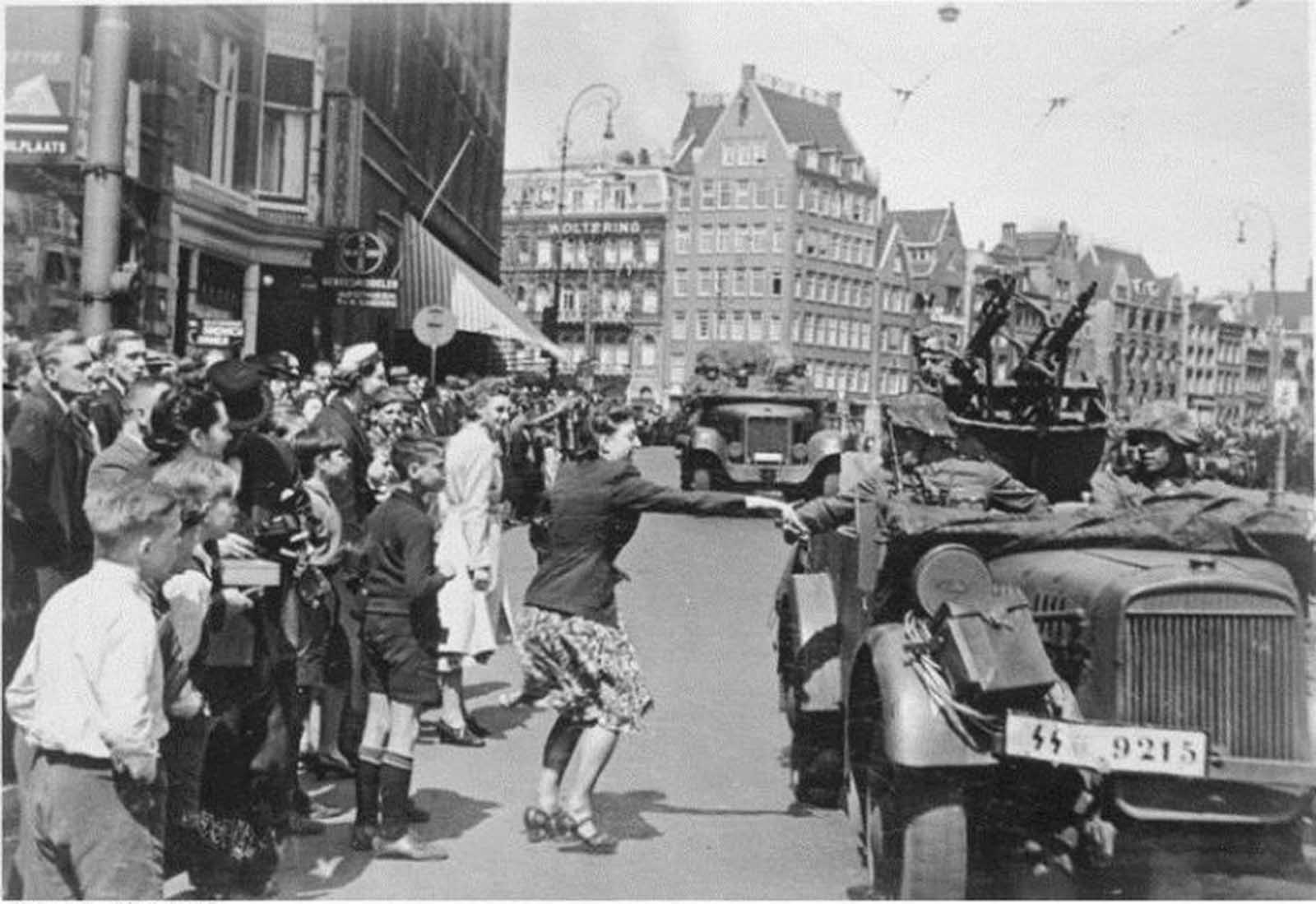 A Dutch girl greets the Wehrmacht boys as they enter Amsterdam, 15 May 1940.