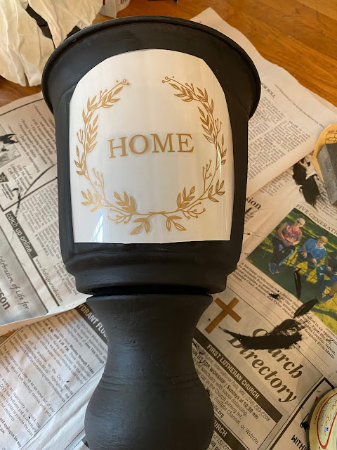 Photo of a black urn with a gold decor transfer on top