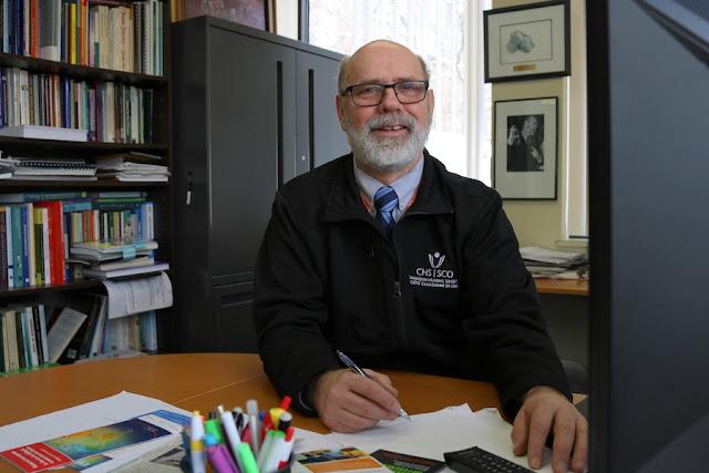 Gary Malkowski en un despacho con un bolígrafo en mano ante una mesa, libros al fondo y sonriendo