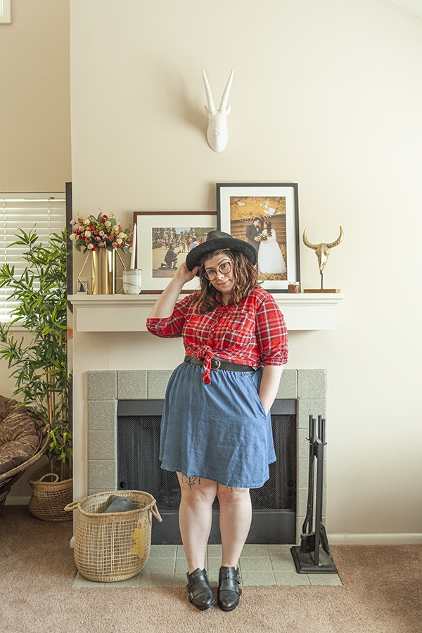 Black wide brim fedora, red plaid flannel button down and tied at the waist, blue denim a line skirt and black booties.