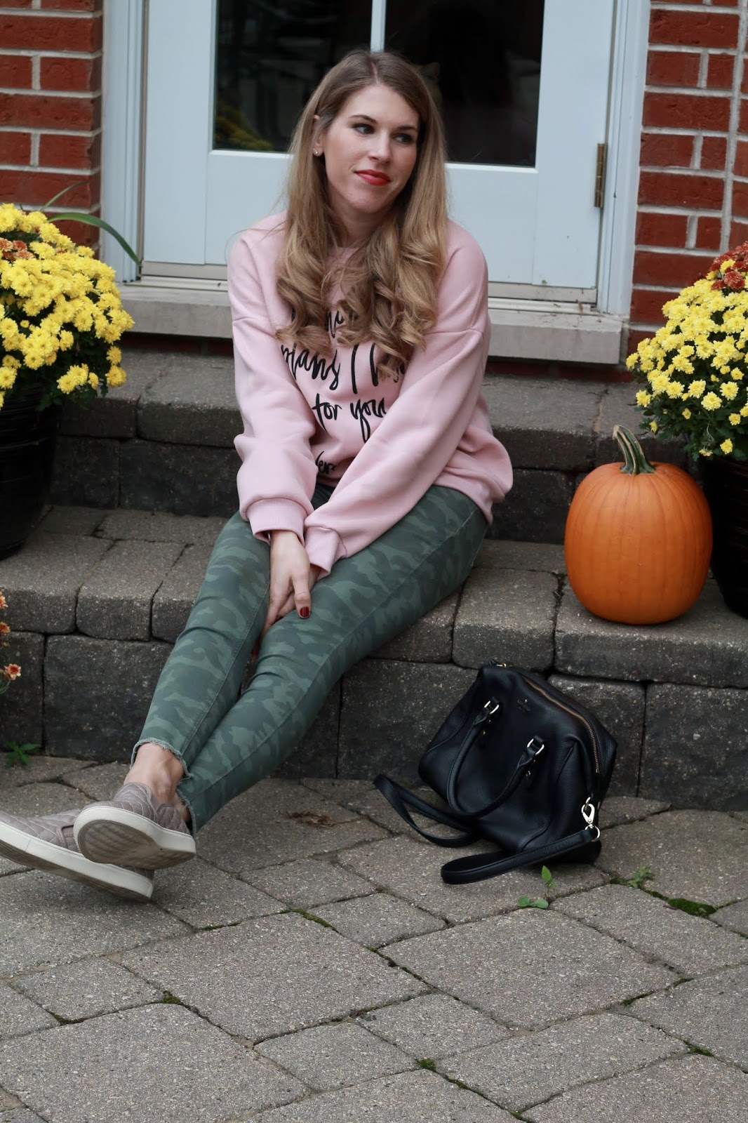 pink graphic sweatshirt, camo pants, grey quilted slip ons, black kate spade crossbody