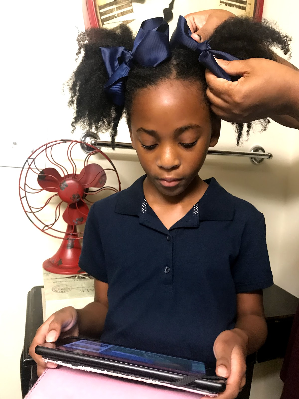Image: Tangie Bell combing her daughters hair as part of her school morning routine