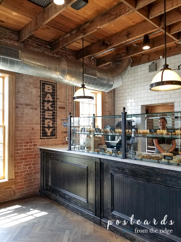vintage style magnolia bakery with black counter, brick wall, and white subway tiles