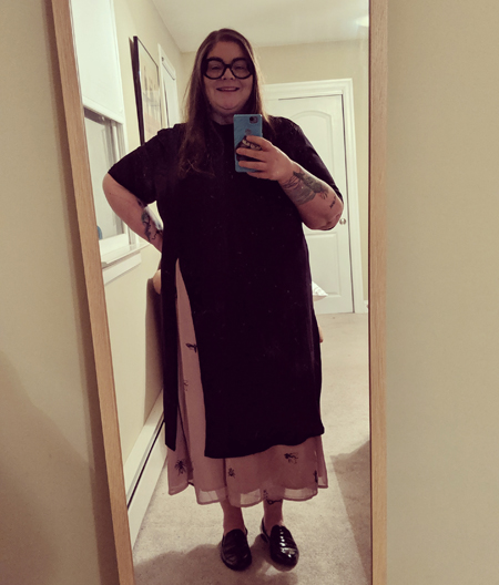 image of me standing in a full-length mirror, with my hair down, wearing black-framed glasses, a long black tunic, a pink skirt with a pattern of black insects on it, and black loafers