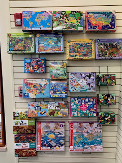 puzzles line a wall at Book People in Sioux City