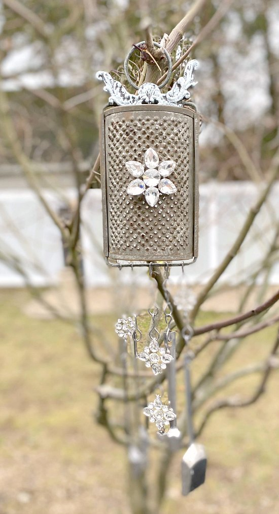 Vintage grater wind chime hanging in tree