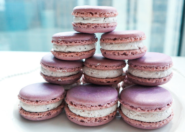 Purple Murple macaros filled with blueberry buttercream on a white plate.