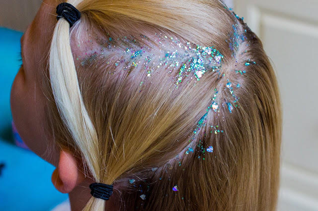 A close up of parted hair with Who's That Girl Glitter Roots applied