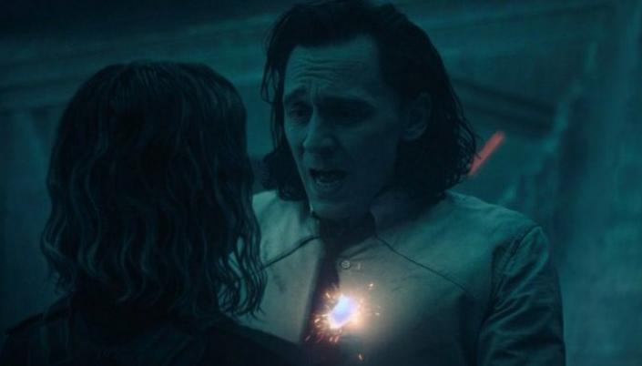Imagem: Sylvie e Loki na sala dos Guardiões do Tempo, um lugar escuro e cavernoso, e Loki é atingido por trás e começa a desaparecer em faíscas.