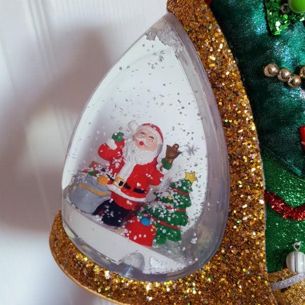 close up of heel of shoe showing Santa inside snowglobe