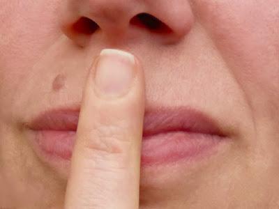 Mund mit Zeigefinger drauf