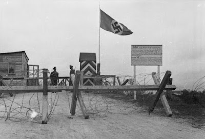 A simple wooden barricade surrounded by barbed wire crosses a street. Beyond it are a Nazi flag, two German soldiers, and a sign in German. Black and white.
