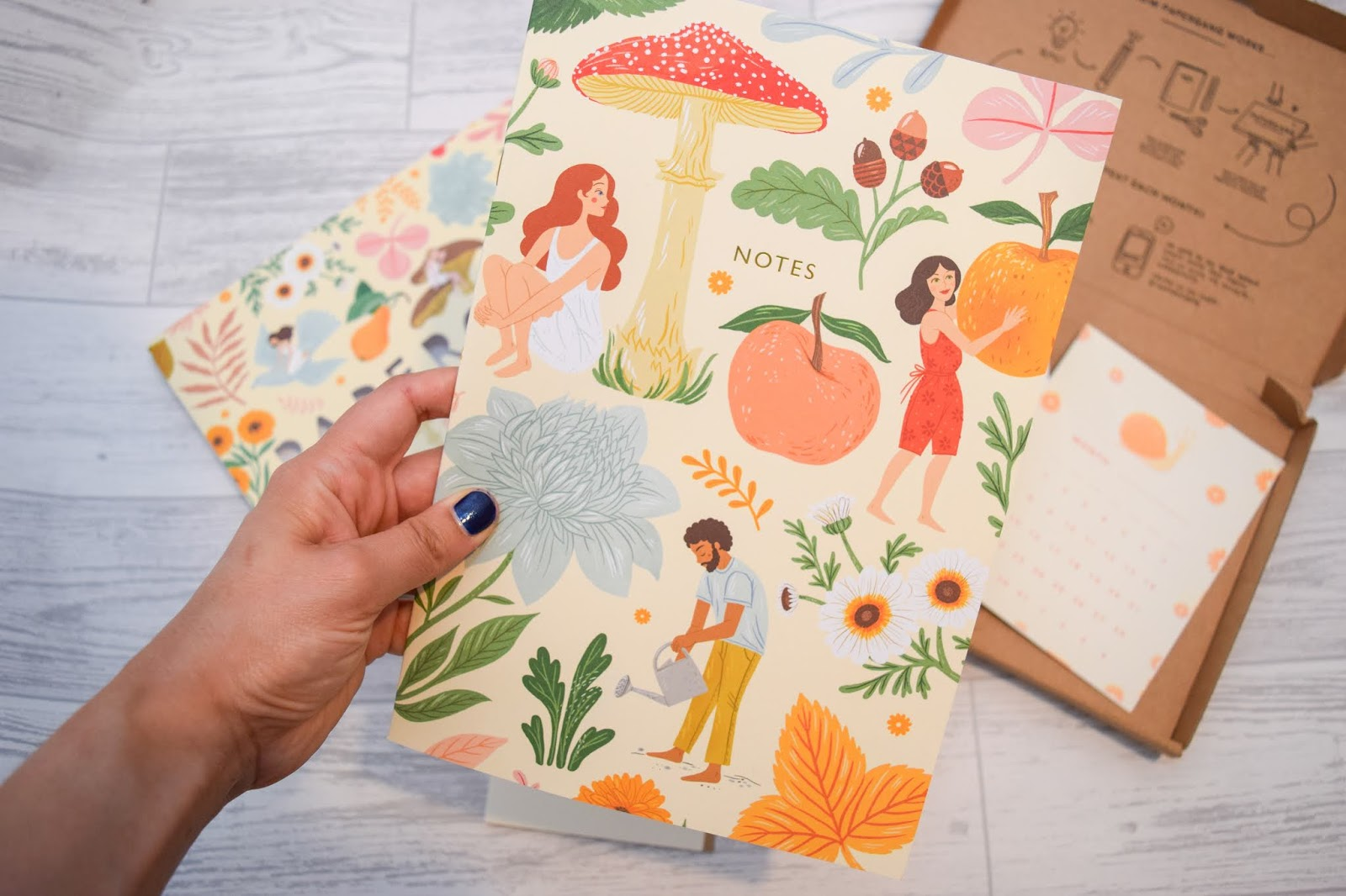 A hand holding an A4 notebook with a vegetable and wildflower design all over and illustrations of people gardening.