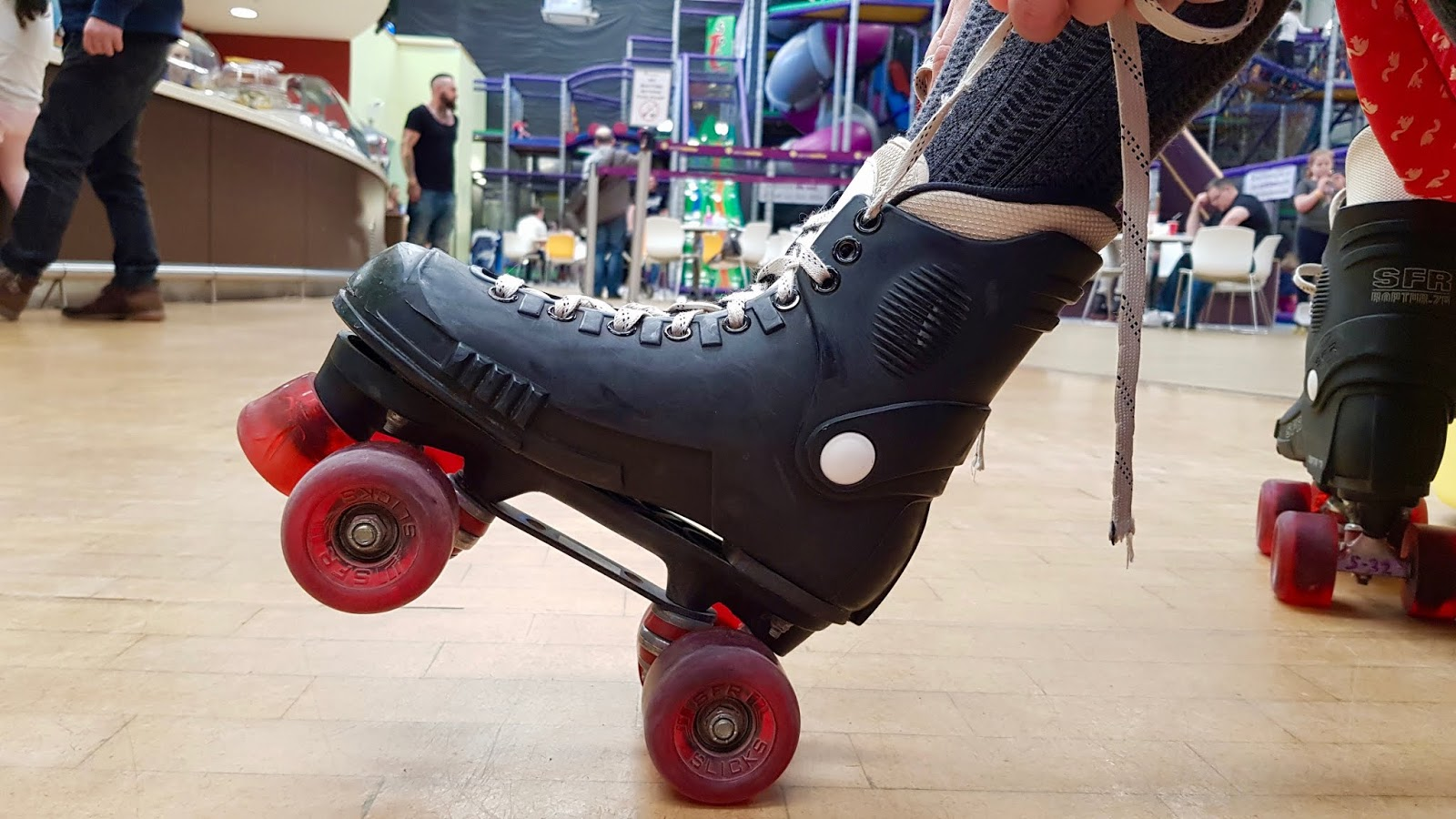 A close-up of Abbey's roller skate at CurveMotion, showing her tying the laces