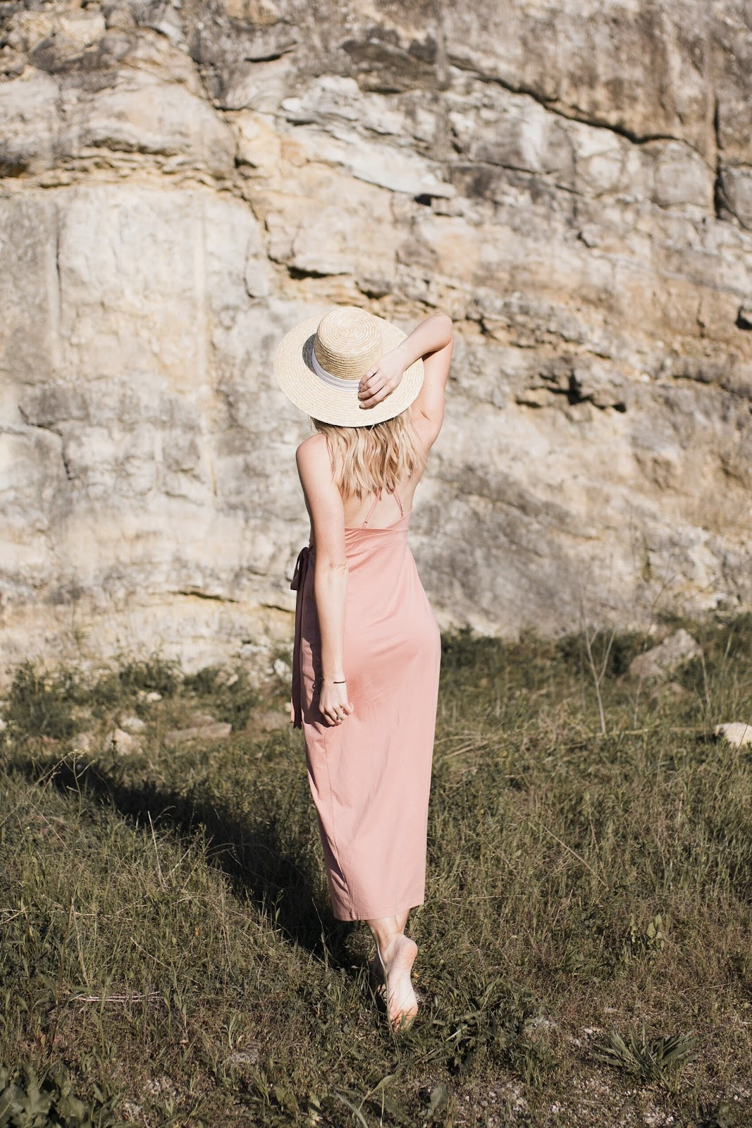 boho vibes in a pink wrap dress and straw boater hat