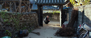 Outside, man crouching at garden archway