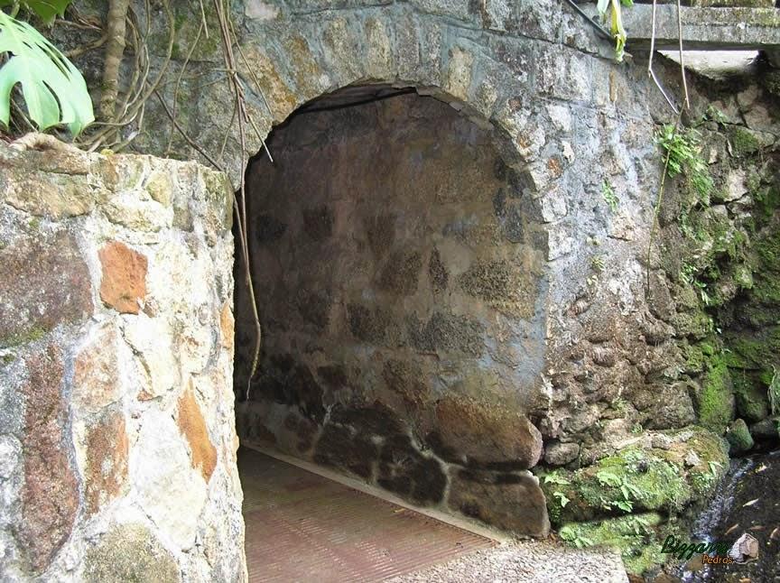 Detalhe do muro de pedra com o pórtico de pedra ligando uma passagem para o outro lado da residência.