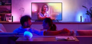 A couple on the sofa watching TV, on the TV is a man with vivid lighting in their Tv and living room with colours blue and pink