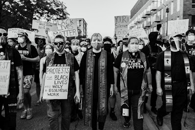 ID: black and white photo taken by Jami Milne shows a crowd of protesters with clergy of varying gender identities in a line in the front. Signs include Black Lives Matter; Your Silence is LOUD; Protests for Black Lives are Holy and Essential Work