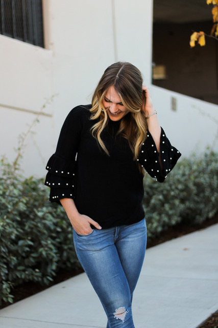 girl smiling, wearing black shein accent sleeve sweater