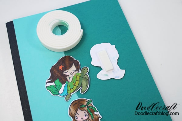 Add foam tape on the back of the little TGF Mermaids and stick them to the notebook.