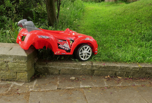 Red and grey pedal car with rear wheels missing.