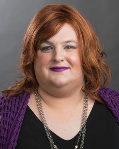 ID: River Needham, M.A. has shoulder length fiery red hair, and is wearing purple themed makeup, including a royal purple lipstick. Chunky silver-colored necklaces can be seen around her neck, as can her black dress and purple sweater. The purple sweater matches her lip color.  Her face is in a neutral expression, and her eyes are focused outward.