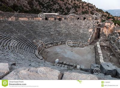 """19.29 Apesar da estrutura dramática rudimentar discernível no livro de Jó e em Cântico dos Cânticos, Israel não produzia peças teatrais, por isso  não possuía nenhum teatro.  A palavra """"teatro"""" vem do grego e é um substantivo derivado do verbo theaomai, que significa """"ver"""" ou """"considerar"""".  O teatro grego e o teatro romano que logo depois,sucedeu o grego  eram estruturas projetadas para acomodar em assentos os espectadores durante as apresentações.  O teatro era geralmente uma estrutura a céu aberto, um semicírculo com assentos de pedra construído ao lado de uma colina e que podia acomodar 5 mil pessoas ou mais.  Os assentos eram cortados concentricamente (direcionados para um centro comum), e na base do auditório uma peça semicircular em desnível acomodava a """"orquestra"""" (o espaço em que o coral, parte indispensável de todas as peças gregas, e os atores atuavam)."""