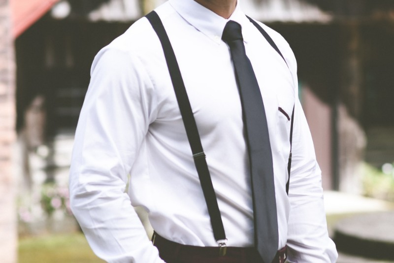 A man wearing suspenders and a tie on white shirt.