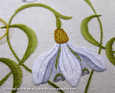 Trellis on top of crewel snowdrop flower stitched in different shades of gold