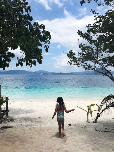 Niña corriendo hacia el mar en Entalula island, El Nido