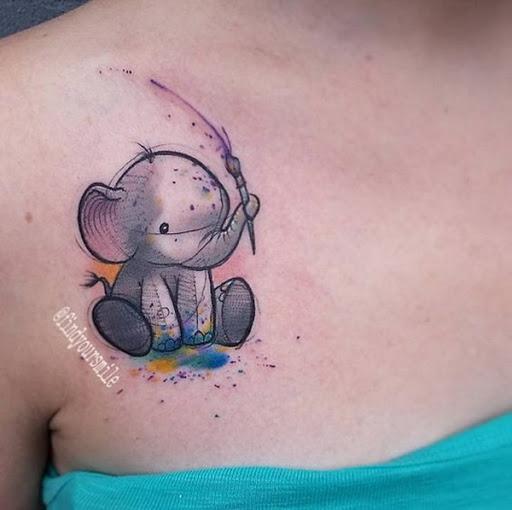 Um estilo cartoon elefante possui um pincel de pintura com seu tronco neste tatuagem embelezado com manchas de aquarela.