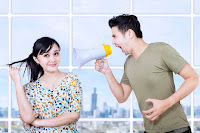 Image of woman being calm under verbal bullying by a man with a megaphone