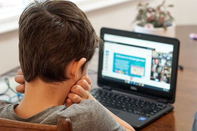 A child looking on the internet on a black laptop