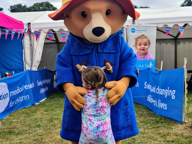 Image of a young girl in a tie dye top and plaited hair hugging a large character. The character is Paddington Bear, he is wearing his signature red hat and blue duffle coat. He is hugging the girl back. In the background is a tent and campaign banners advertising action medical research for children