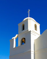 Bell tower of a white church with a white cross at the top