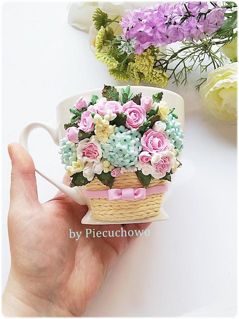 kubeczek z kwiatową kompozycją w koszyczku.